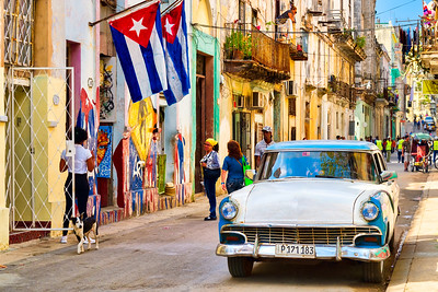 HAVANA,CUBA - MARCH 16,2018 : Urban scene with cuban flags, classic car and colorful decaying buildi