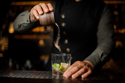 Barman Adding A Cane Sugar Into The Cocktail Glass With Fresh Lime For Making A Fresh Cocktail