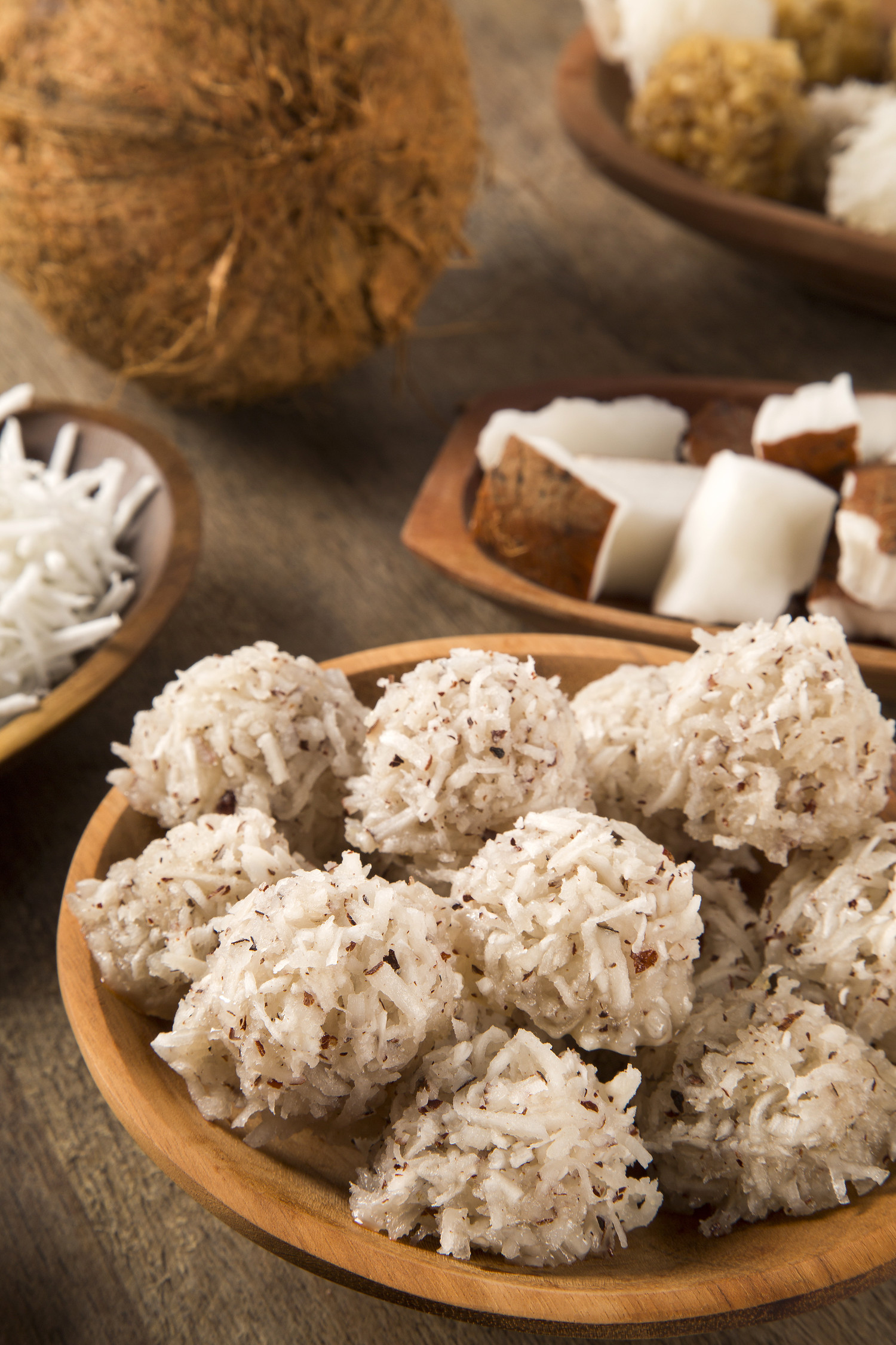 Panamanian cocada dessert, dessert balls covered in coconut in a bowl with coconut in the background.