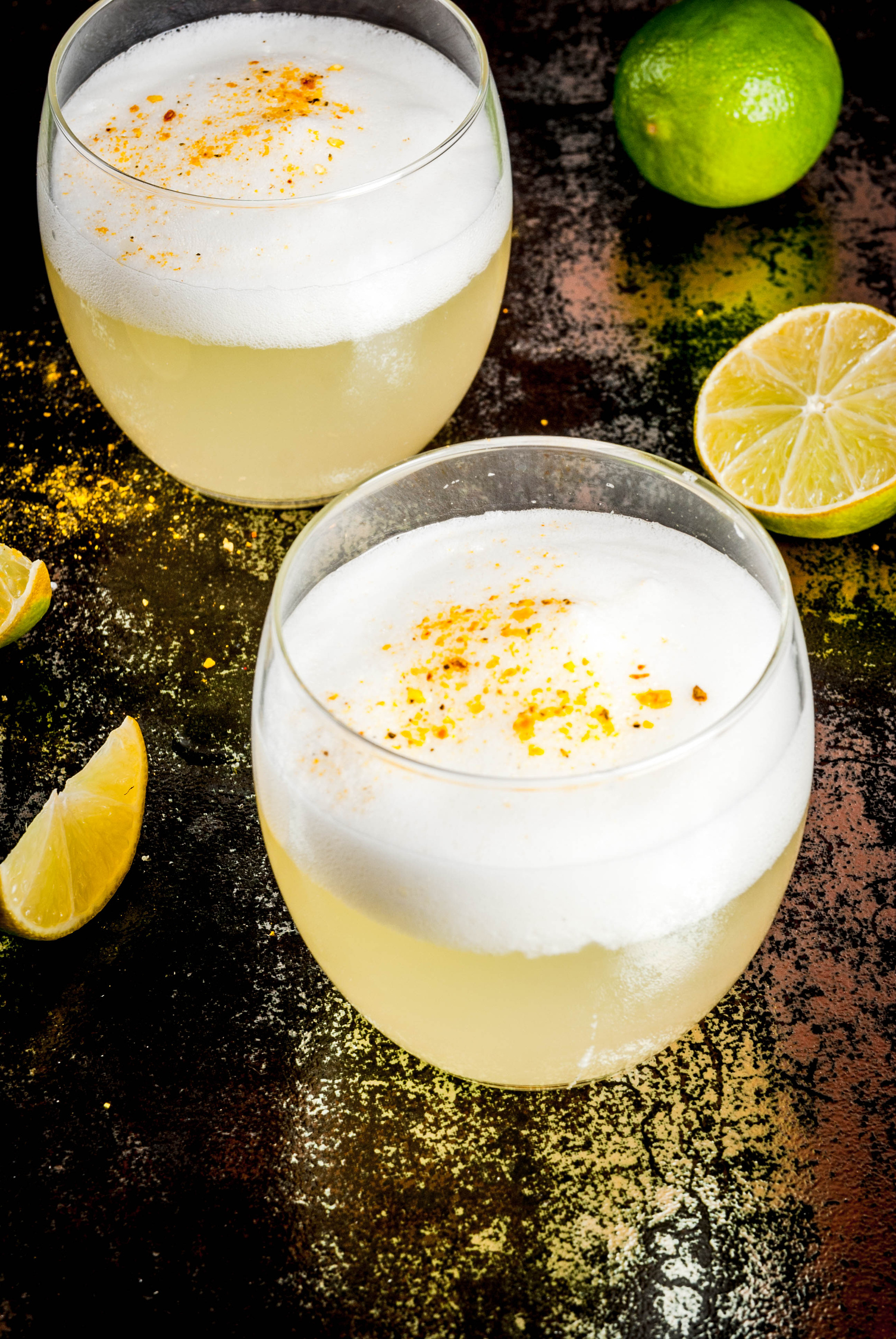 Pisco sour one of the best cocktails around the world on a dark background with lemons