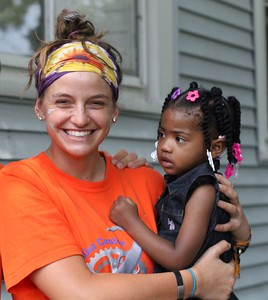 Lydia Huelskamp, the 2015 Fuller Center Bicycle Adventure volunteer leader, with a homeowner's child during a 2014 build day in North Chicago.