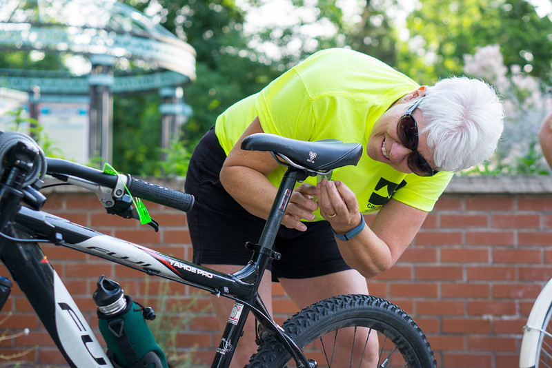 Pam Miller installs a reflector on her bike seat Wednesday June 22, 2016. Miller works for City of Loveland Public Works and volunteered to work at the booth on First Street and Washington Avenue for Bike to Work Day. <br /> <br /> Photo by Michael Ortiz/ Loveland Reporter-Herald