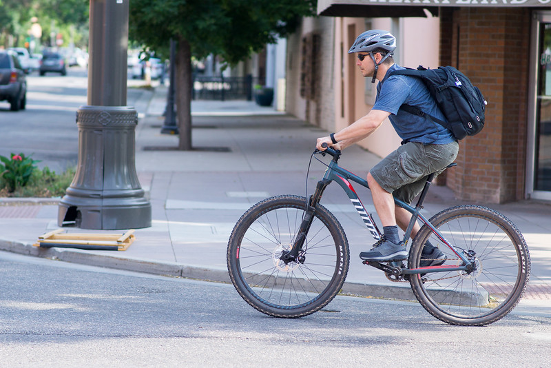 Doug Collins rides his bike down Fourth Street in Loveland Wednesday June 22, 2016. Collins lives only four blocks from work and normally walks but biked to work just for the occasion. <br /> <br /> Photo by Michael Ortiz/ Loveland Reporter-Herald