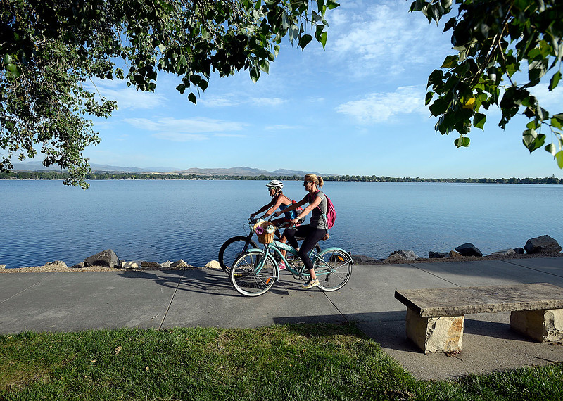 Robin Frahm, left, and Ryann Carlson ride their bikes on the south shore of Lake Loveland Wednesday, June 28, 2017, on their way home from work after stopping at the Bike to Work breakfast station at the southeast corner of the lake in Loveland.  (Photo by Jenny Sparks/Loveland Reporter-Herald)