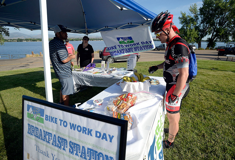 Chris Fiene of Loveland grabs some food Wednesday, June 28, 2017, at the Bike to Work breakfast station on the southeast corner of the Lake Loveland.  (Photo by Jenny Sparks/Loveland Reporter-Herald)