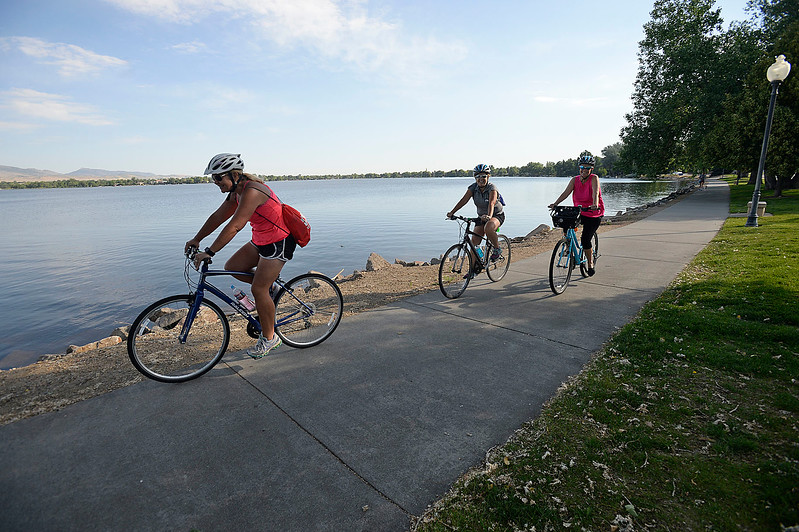 Mimi McMaster, left, Terri Bellinghausen, center, and Janna Dunkle ride their bikes on the south shore of Lake Loveland Wednesday, June 28, 2017, after stopping at the Bike to Work breakfast station at the southeast corner of the lake in Loveland.  (Photo by Jenny Sparks/Loveland Reporter-Herald)