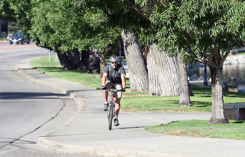 Marco Scalise rides his bike on the south shore of Lake Loveland Wednesday, June 28, 2017, on his way to work in Loveland.  (Photo by Jenny Sparks/Loveland Reporter-Herald)