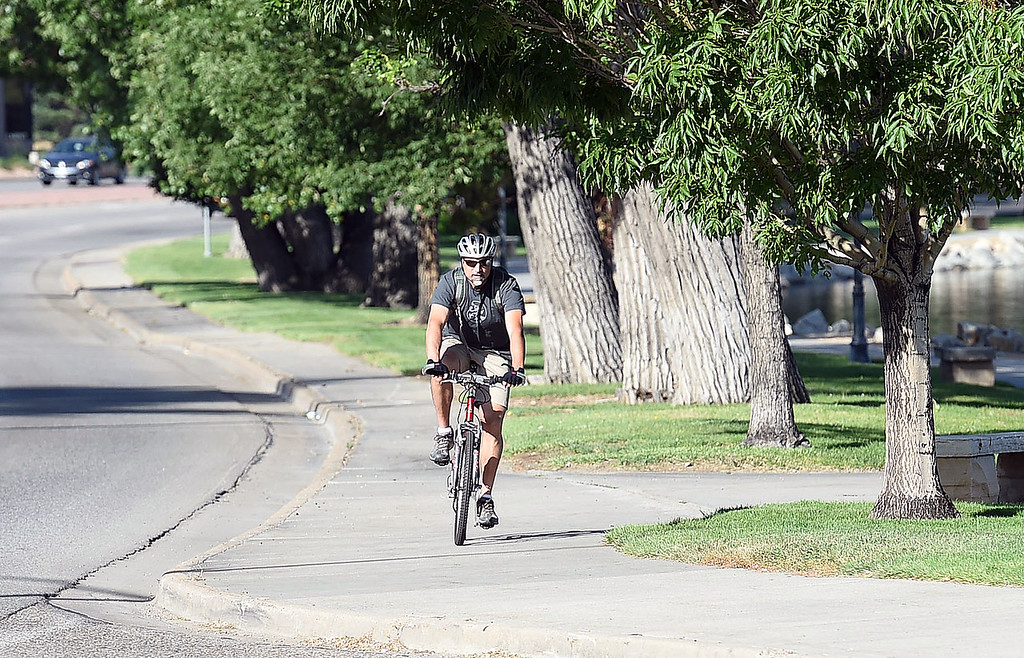 . Marco Scalise rides his bike on the south shore of Lake Loveland Wednesday, June 28, 2017, on his way to work in Loveland.  (Photo by Jenny Sparks/Loveland Reporter-Herald)