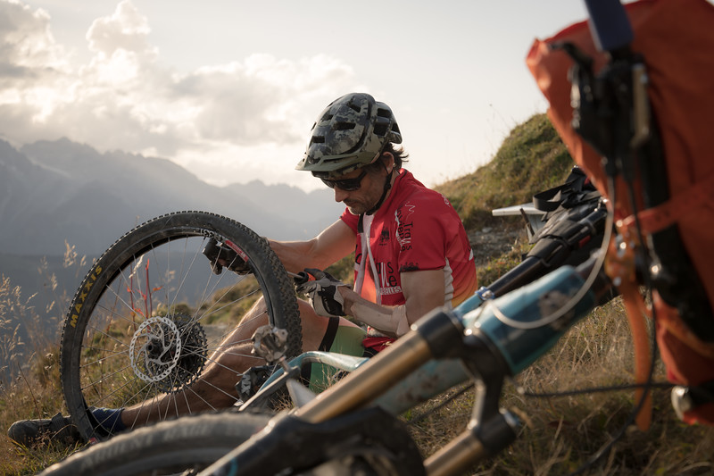 Fixing a broken spoke by Col de Mille on the Tour des Combins, Switzerland
