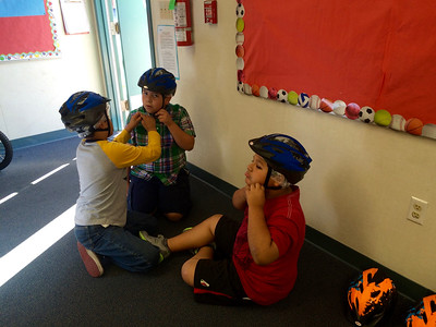 Students helping each other with helmet fitting