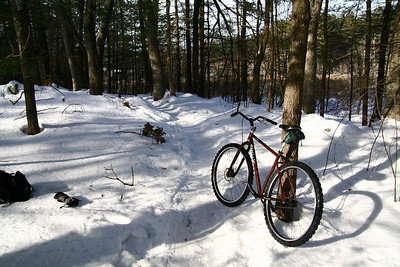 It rides great.  I took it out to Great Brook Farm today, and rode around on the handful of trails that stay open to bicycles in the winter.  Those trails see lots of hiker and snowshoe traffic, which packed the snow down to provide a pretty firm surface, most of the time.  The tires hooked up great, in those conditions (I had them at 15psi).  Traction was actually better than what I usually experience in dry summer conditions.  The fixed drivetrain was neat, too -- while the inability to coast (and rigid frame) made me take descents pretty slow, the rest of the time I really enjoyed the feedback and modulation it provided.  It was particularly amazing on the climbs.  I didn't fail at a single climb all day.  Overall, it was a great time.  I went out expecting to ride one or two laps and be so exhausted that I had to stop.  I did 3 and felt like I had energy for more.