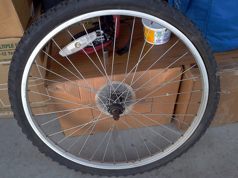Here's the original rear wheel;  note rust, absence of quick-release axle & skewer; corrosion on spoke-nipples;  rim drilled for Schrader valve.
