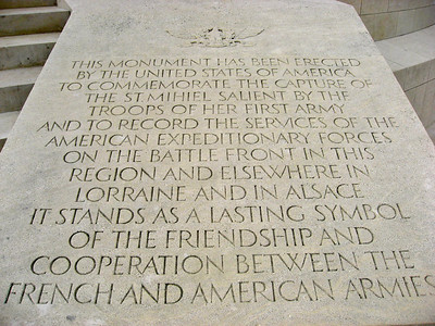 """On the right side of a flight of steps leading to the monument is engraved: """"THIS MONUMENT HAS BEEN ERECTED BY THE UNITED STATES OF AMERICA TO COMMEMORATE THE CAPTURE OF THE ST. MIHIEL SALIENT BY THE TROOPS OF HER FIRST ARMY AND TO RECORD THE SERVICES OF THE AMERICAN EXPEDITIONARY FORCES ON THE BATTLEFRONT IN THIS REGION AND ELSEWHERE IN LORRAINE AND IN ALSACE. IT STANDS AS A LASTING SYMBOL OF THE FRIENDSHIP AND COOPERATION BETWEEN THE FRENCH AND AMERICAN ARMIES."""" The same inscription is repeated in French on the left side of the flight of steps. Near the top of the monument on the outside lintel are engraved the names of villages and towns where battles were fought in this region: """"THIAUCOURT – VIGNEULLES – FRESNES – VIEVILE – ST. BENOIT – NORROY – BENEY – JAULNY – FRAPELLE – HAUMONT – ST. HILAIRE – XAMMES – NONSARD – VILCEY – ST. BAUSSANT – VANDIERES."""" Inside the memorial is a useful map and a stone relief map."""