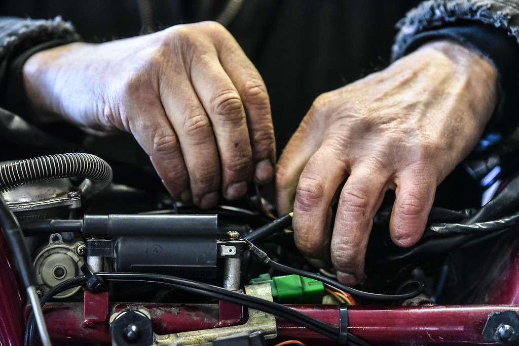 . (03/19/18 AYER MA) The hands of Bikeworx owner Galen Miller show him working on the wiring of a bike in his Ayer based shop on monday. SENTINEL & ENTERPRISE JEFF PORTER