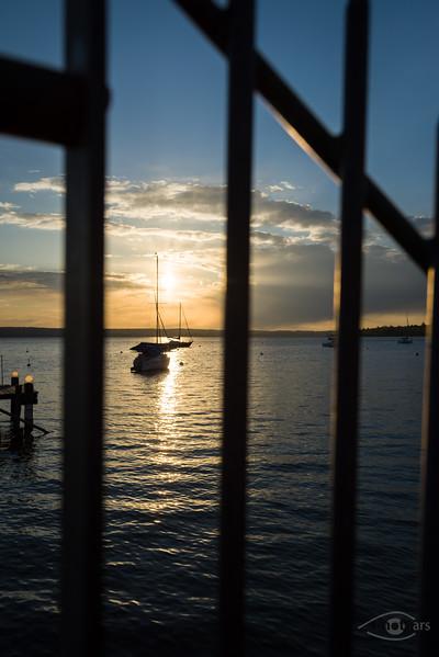 Sonnenuntergang am Ammersee durch Gitter, Herrsching, Bayern, Deutschland