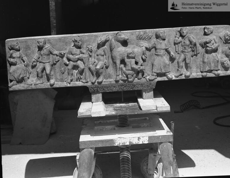 #100668   T-Kreuz; mit der Legende vom Schmitten-Annali; auf dem Relief des Querbalkens; hier noch im Atelier von Albin Näpflin, Altishofen; Standort:; An der nordöstlichen Ecke des Schulhausareals Hofmatte; mwil; fja; s.T-Kreuz