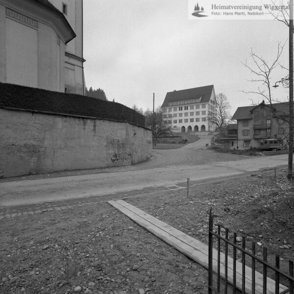#100822 | Vor der Sanierung der Strasse und der Friedhofsmauer 1964/65; links; Pfarrkirche, erbaut 1801–1803; Baumeister Joseph Purtschert aus Pfaffnau; Hintergrund mitte; das alte Schulhaus; erbaut 1926 durch Architekt Armin Meili; rechts; Kaufhaus Bürli-Rey; hust; PBA