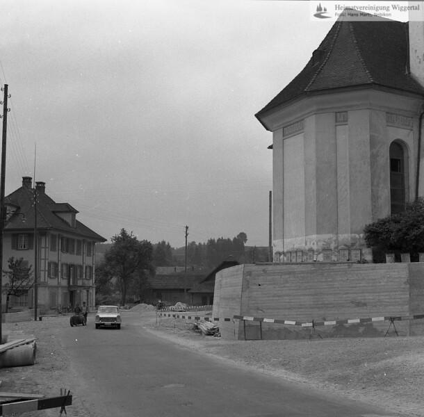 #100891 | Sanierung der Hinterdorfstrasse nach Fischbach und der Friedhofsmauer 1965 rechts; Pfarrkirche; erbaut 1801–1803; Baumeister Joseph Purtschert aus Pfaffnau; links; Bäckerei Bürli; elaf; hust