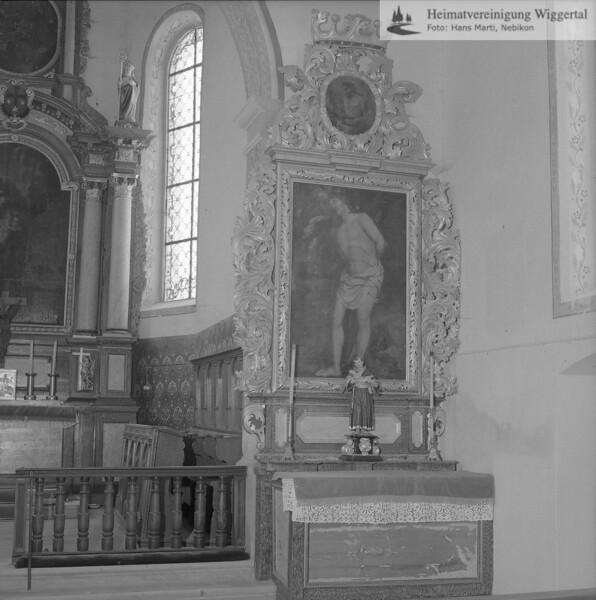 #110078 | Südlicher Seitenaltar mit dem Sebastiansbild von Johannes Brandenberg; das Oberblatt zeigt den heiligen Johannes den Täufer; Vor dem Altar-Bild eine kleine Antonius-Statue; Die beiden Seitenaltäre wurden von Michael Hartmann geschaffen; elaf; fja