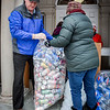 From left, Peter Coppinger of Billerica and Elizabeth Gottmann-Hanrahan of Billerica help each other bag up large amounts of cans outside the Billerica Public Library, wich will help fund programs that are not in the library's budget. SUN/Caley McGuane