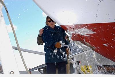 Bill Lane/ Democrat photo. Mrs. Nancy Imes, mother of Magnolia's owner Sid Imes of Columbus, Mississippi, christen's the 56 ft schooner in York Harbor Wednesday.