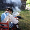 Rob Sigmon of Townsend fixes his leather drum strap by the fire at the Billerica Colonial Minute Men's encampment at Old Sturbridge Village during the Redcoats & Rebels event. -- photo by Mary Leach