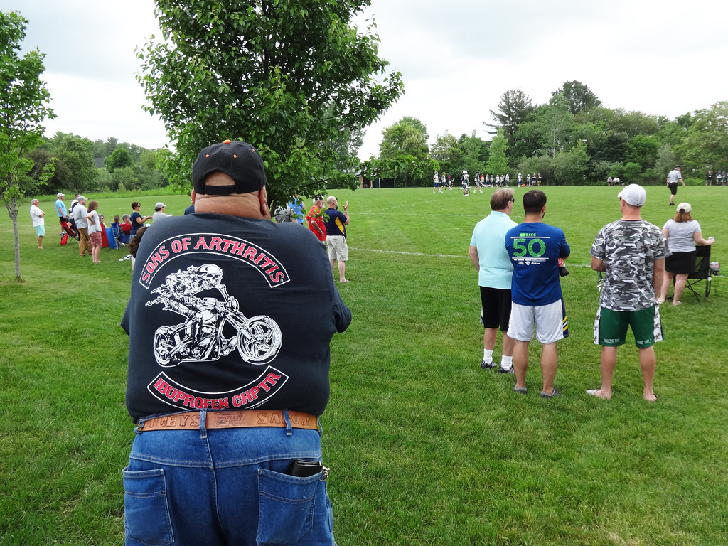 . A man watched a ball game at the field next to the parking lot where motorcycles were parked. Photo by Mary Leach