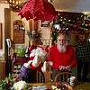 """Chuck Graham sings along with a dancing Santa who kicks up his feet as """"Jingle Bells"""" plays in the kitchen. -- photo by Mary Leach"""
