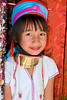 A young girl of the Long Neck (Karen) tribe  in Chiang Rai Thailand, showing off her golden neck decorations.