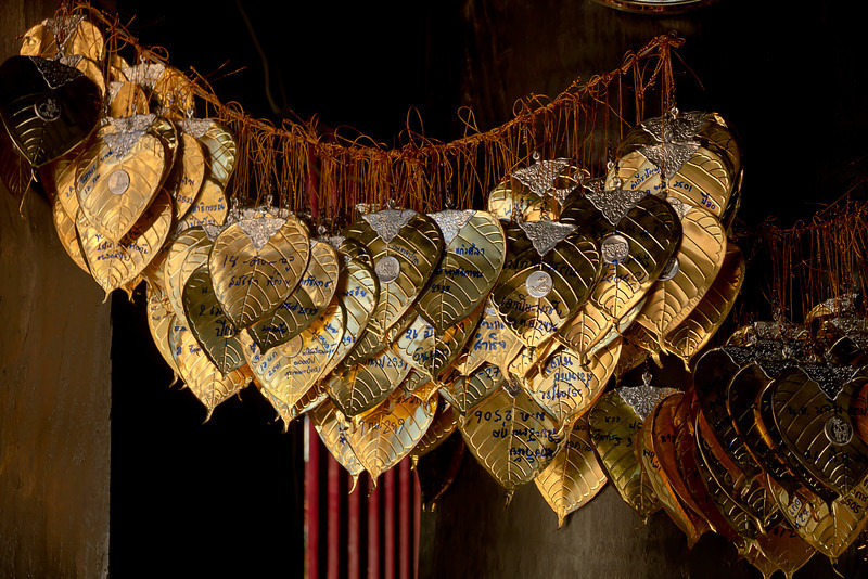Gold leaf-covered lotus petal plaques identifying donors at the three Kings Monument in Chiang Mai, Thailand