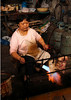 Woman brazing meat in market in Fengdu, China