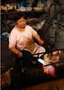 Woman brazing meat in market in Fengdu, China