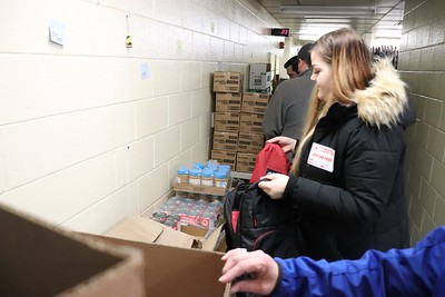 Volunteers from Bimbo Bakeries go to work on packing nearly 100 backpacks with food for students enrolled in the program in advance of the holidays.