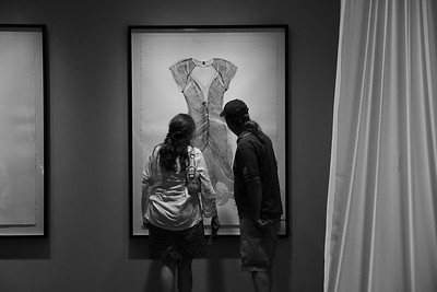 Art lovers looking at monotype prints of dresses at the Museum of Glass, Tacoma
