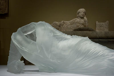 Ancient stone sarcophagus exhibited with  modern sculpture of dress glass at the Chrysler Museum