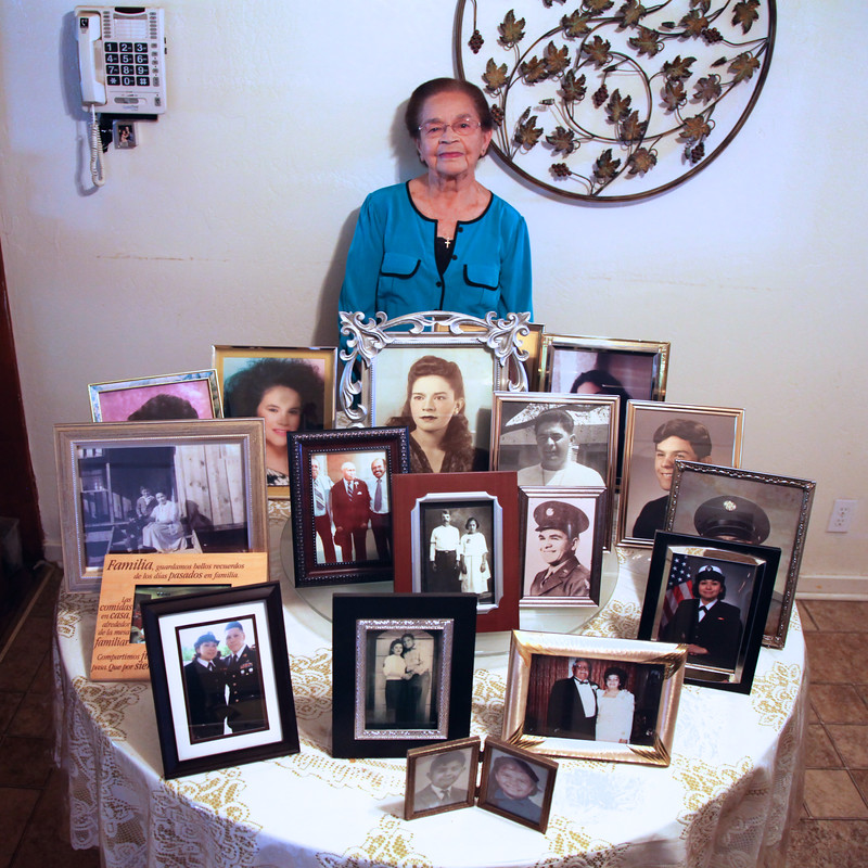 Maggie poses with photos of family
