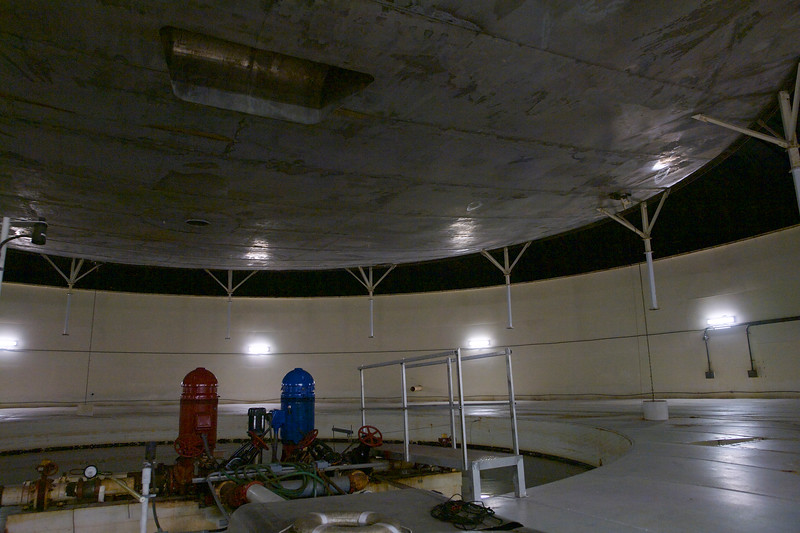 Inside one of the Lung Domes. Pumps for circulating water from the basin here to the structures for temperature regulation. The elevated metal disc is sealed towards the dome roof with a large elastic rubber membrane and can be raised and lowered by a motor to keep the pressure inside the sealed Biosphere 2 constant over the day and night temperature cycles.