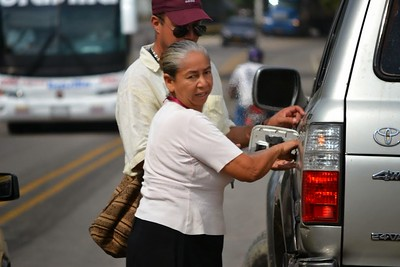 Cheap black market, contraband Venezuela gas - going slowly through a town suddenly this lady runs out with a jerry can of gas. Trivia - Venezuela has world's cheapest gasoline, which its government is believed to be subsidizing to the tune of $8 billion a year. A gallon of 95-octane gas sells for 18 cents per gallon, while 91-octane costs just 12 cents per gallon. In contrast, in Colombia, where the price is set by the free market and which has less oil, gasoline sells for around $4.15 per gallon. Throw into the mix a black market exchange rate (another thriving business in this border area) that reduces prices by a further two-thirds, and it's easy to see how contraband gas has become such a lucrative business here.