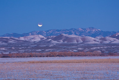 A lunar eclipse of a setting moon over the mountains near dawn.