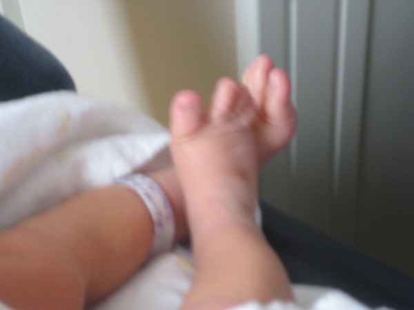 Blurry little feet with hospital tags still on.