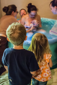Thielke's children, Jaden and Willow watch as their mother comforts their new-born brother.  Jaden and Willow remained present for the birthing process.