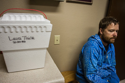 Laura's husband, Jason, waits near a cooler holding Laura's placenta.  The placenta will be taken and process into dehydrated capsules that Laura will take in the preceding months. This is thought to help mitigate the side effects from the dramatic drop in hormones after birth which have been associated with baby blues and postpartum depression.