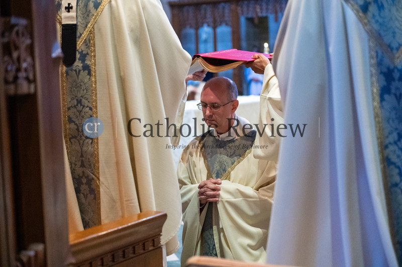 Bishop Bruce A. Lewandowski, C.Ss.R., closes his eyes as the Book of the Gospels is placed over his head during his Aug. 18 episcopal ordination at the Cathedral of Mary Our Queen in Homeland. (Kevin J. Parks/CR Staff)