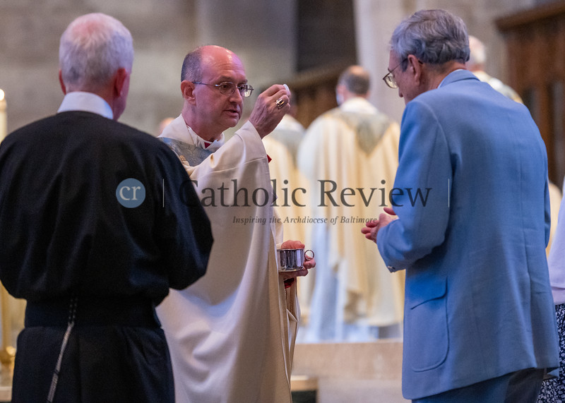 Bishop Bruce A. Lewandowski, C.Ss.R., offers communion to his father, Robert Lewandowski, during his Aug. 18 episcopal ordination at the Cathedral of Mary Our Queen in Homeland. (Kevin J. Parks/CR Staff)