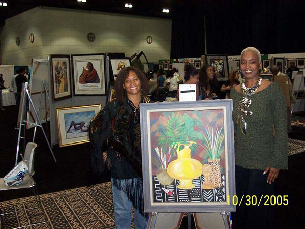 Aldonia Bailey, pictured with her oil painting, standing next to Sandra McDaniels.