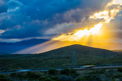 Sun rays shine through a break in the storm clouds above the i-17, near the Bloody Basin Rd exit. Bradshaw Mountains in background.