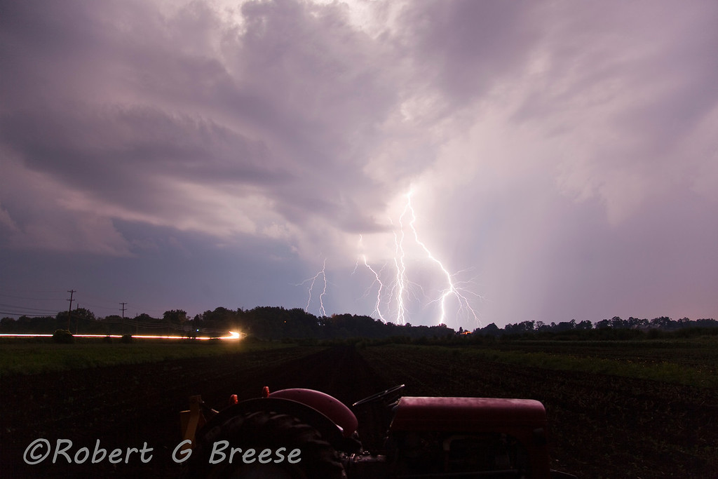 Lightning strikes in the heart of the black dirt region of Pine Island. Car headlights are seen left of photo traveling along Cunty Rt1 with a farm tractor in the foreground.