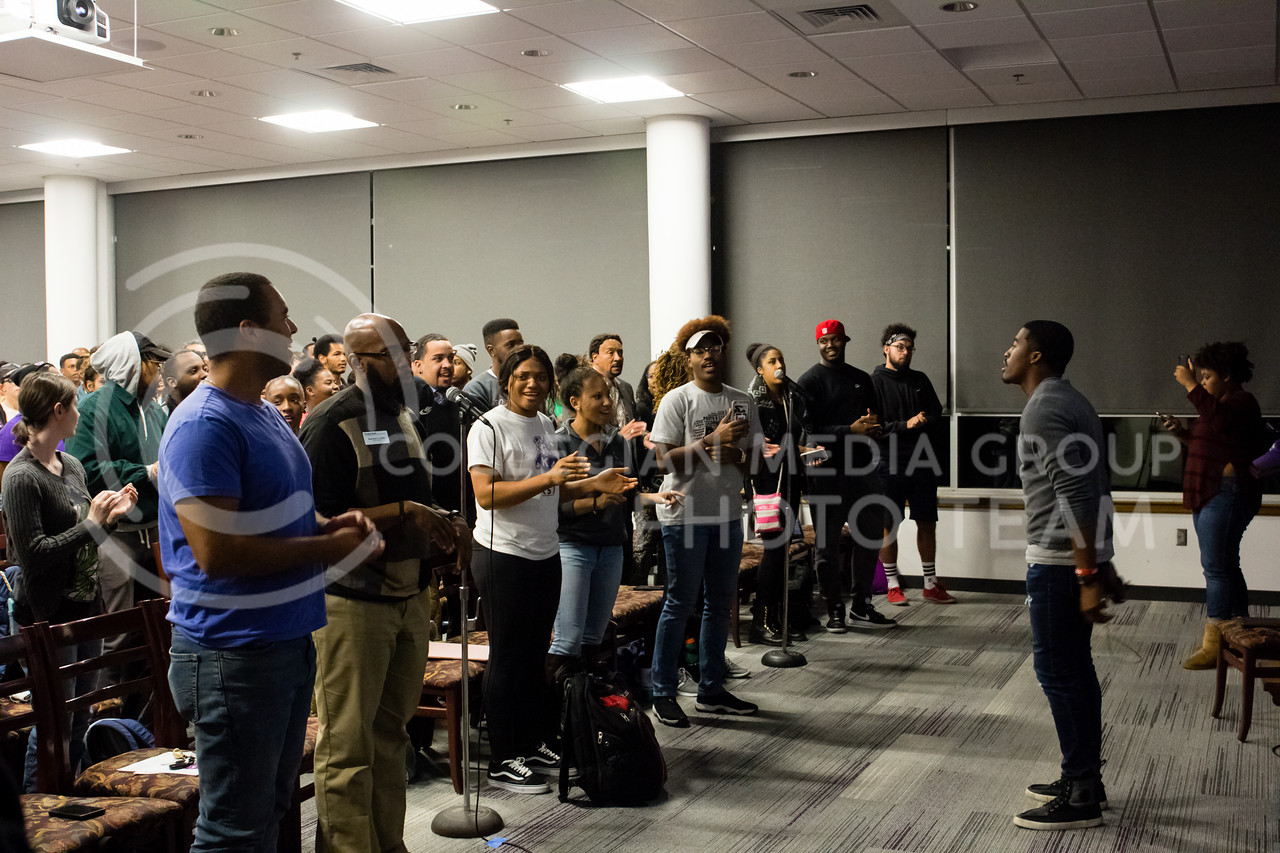 Darrel Reese Jr, president of the Black Student Union leads BSU members and others in singing their BSU National Anthem at the BSU Emergency Meeting in the Bluemont Room of the Union on Nov. 1st, 2017. (Alex Shaw | Collegian Media Group)