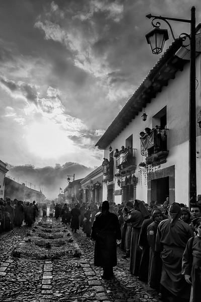 Celebration of the passion of Jesus Christ in the old baroque streets of Antigua Guatemala. Sunset approching, long lines of penitents from the church of San Bartlome Becerra. UNESCO World Heritage