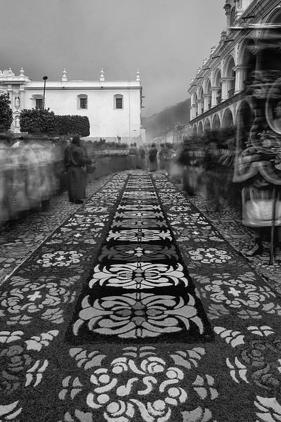 "Carpets for God. Flower carpets in Antigua Guatemala during the Holy Week, handcrafted for several hours preceding the procession. Beautiful sight of penitents moving on the sides until the heavy wooden ""andas"" with almost hundred porters walk through them and the image of Jesus Christ bless all who did it. Colonial Spanish heritage blended with colorful Mayan traditions and respect for their gods. UNESCO World Heritage."